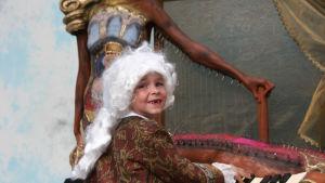 Liten pojke målad till Mozart vid piano