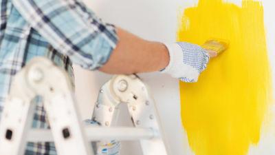 Man som målar gul färg på en vägg.