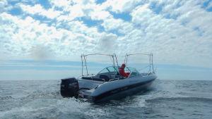 Man i båt på öppet hav
