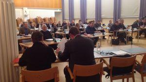 Stadsfullmäktigeledamöter i en sal.