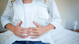 Gravid kvinna håller sig för magen