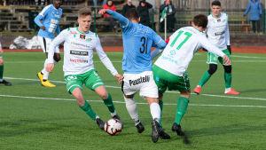 Tre spelare försöker komma åt bollen.