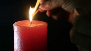 en mänsklig hand tänder ett rött blockljus