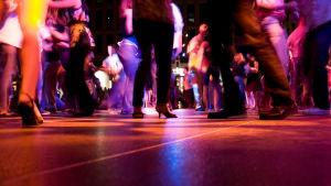 nerifrån syns golvet och en massa skor och kläder från där folk dansar på ett dansgolv i mörkt ljus