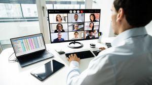 en man sitter vid ett skrivbord och deltar i ett möte på distans där han ser flera ansikten i skärmen