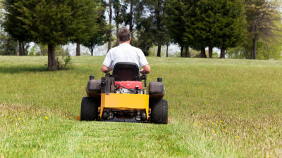 En man som kör en motoriserad gräsklippare.