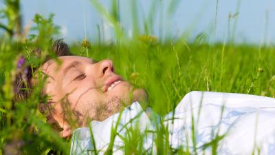 Man som ligger på rygg i gräset.