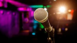 en mikrofon i färgglatt men dämpat ljus runtomkring
