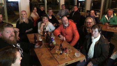 Glada människor sitter vid bord på en restaurang med öl på borden och tittar in i kameran.