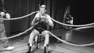 """Nyrkkeilijä Pertti """"Purtsi"""" Purhonen istuu kehän nurkassa ohjelmassa Iskelmäkaruselli."""