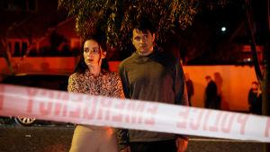 Nainen ja mies seisovat poliisin rajaaman alueen ulkopuolella hieman kauhistuneen näköisinä.