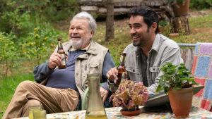 Bahman dricker öl och skrattar glatt tillsammans med grannen Onni.