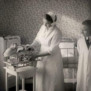 Arvo Ylppö övervakar då en nyfödd baby vägs, 1930-tal