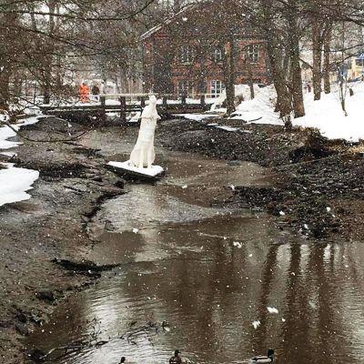 En å som är nästa utan vatten. Det snöar. En vit skulptur i vattnet. I bakgrunden en bro där två personer står.