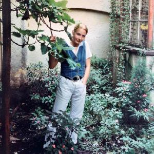 Nuori Anni Valtonen poseeraa puun lehtien lomitse bogotalaisen kotinsa pihamaalla.