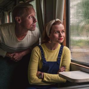 Mies ja nainen istuvat junassa. Kuvan vasemmalla puolella kuva Suomen kartasta. Keskellä karttaa Egenlandin logo.