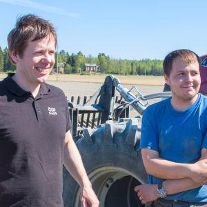 Fredrik Grannas och Einar Brors framför en traktor.