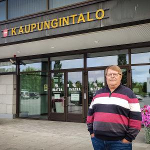 Ilkka Nokelainen seisoo kädet taskuissa kaupungintalon edessä laajakuvassa