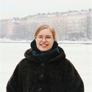 Silmälasipäinen nainen seisoo lumisessa maisemassa.