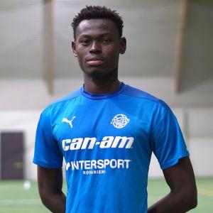 Siniseen RoPsin pelipaitaan pukeutunut nuori jalkapalloilija Mohammed Adams poseeraa kameralle vakavin ilmein kädet selän takana jalkapallokentällä