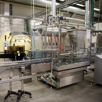 Pullojen täyttökone tuotantolinjalla.