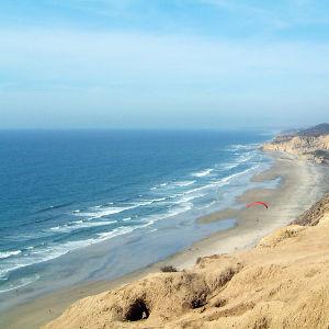 Aurinkoinen kuva meren rannalta rantatöyräältä. Kuvassa näkyy myös muutamia purjelentäjiä.
