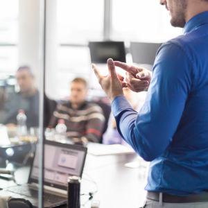 En chef står och talar inför några människor kring ett mötesbord.