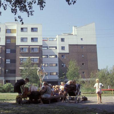 Kerrostalon piha 1980-luvulla, lapsia äiteineen syömässä pihan puistossa.