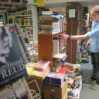 Antikvariaatti Lukulaarin myyjä kirjojen keskellä