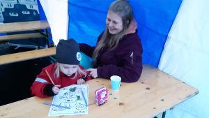 En kvinna och en liten flicka sitter vid ett bord inne i ett tält. Flickan färglägger en målarbild.