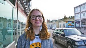 En ung kvinna står på en gata i Lovisa. Hon tittar in i kameran och ler. Bakom henne syns bilar och hus.