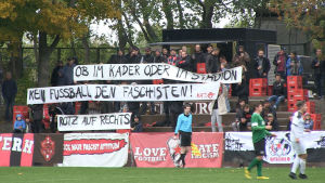 En liten fotbollsläktare med plakat med politiska budskap.