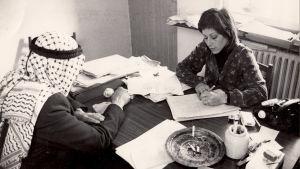 Asianajaja Lea Tsemel tekee muistiinpanoja. Työpöydän ääressä selin on hänen huivipäinen päämiehensä.