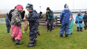 Barn leker på en gräsmatta.