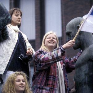 Naisia Kolmen sepän patsaan päällä Suomen lipun kanssa juhlistamassa jääkiekon MM-voittoa 1995