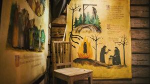 Piirrettyjä suurikokoisia julisteita lautaseinillä, piirroksia noitavainoista: rovio, jolla poltetaan hahmoja, hirsipuu, tekstiä