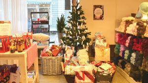 Mellan en hylla med saftflaskor och en hylla med garn står en julgran med julljus och små papperslappar som hänger från grenarna. På golvet vid granen står flera korgar och stora påsar fyllda med julklappar.