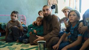 Mies lapsia ympärillään istuu huoneessa lattialla. Kaikki katsovat samaan suuntaan kameran ohi.