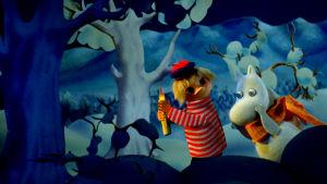 Tooticki och Mumintrollet går genom en vintrig skog sent om kvällen.