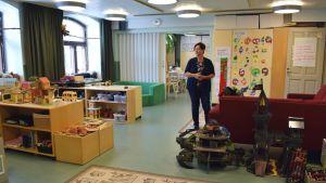 En barnpedagog står mitt i förskolans lekrum fyllt med leksaker och skåp.