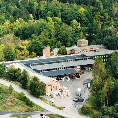 Ett fabrikskomples med byggnader från olika tider, främst i rödtegel. Fordon och varor står på gården. Lummig miljö, till höger syns Svartån.