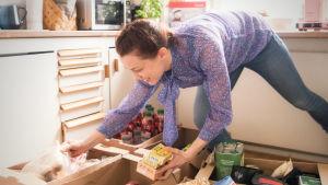 En kvinna ler medan hon böjer sig ner och plockar matvaror från lådor i kartong.