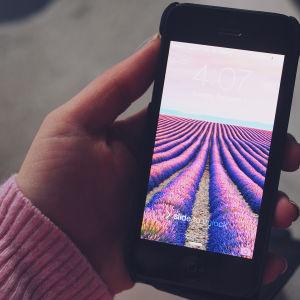 En hand håller i en en mobiltelefon