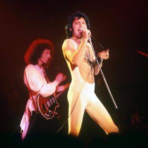 Brian May och Freddie Mercury i Queen live 1977. Mercury har vit jumpsuit.