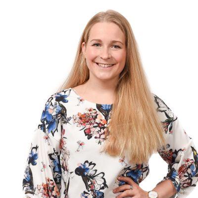 En ung kvinna med långt ljust hår skrattar mot kameran. Anita Westerholm leder Svensk Ungdom i Raseborg