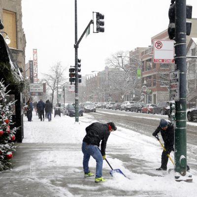 Kaksi miestä lapioi lunta kaupungin kadulla