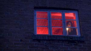 Toimittaja Kaisa Pulakka ullakkohuoneessa kynttilänvalossa ikkunan edessä