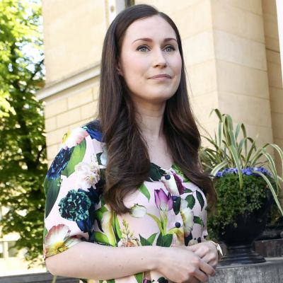 Sanna Marin står på Ständerhusets trappor och blir intervjuad. Hon ser åt sidan och ler.