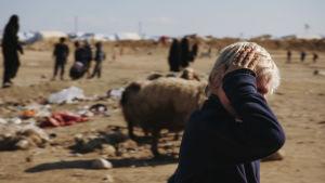 En liten pojke med blont hår o handen för ansiktet ser in i kameran. I bakgrunden syns ett sandlandskap med skräp på marken, får och människor.