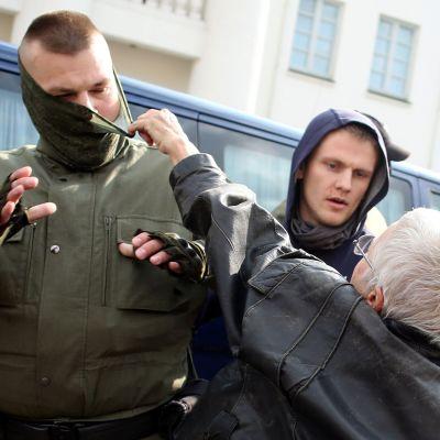 Kvinna försöker riva av masken på en man som griper demonstranter  12.9.2020 i Minsk, Belarus